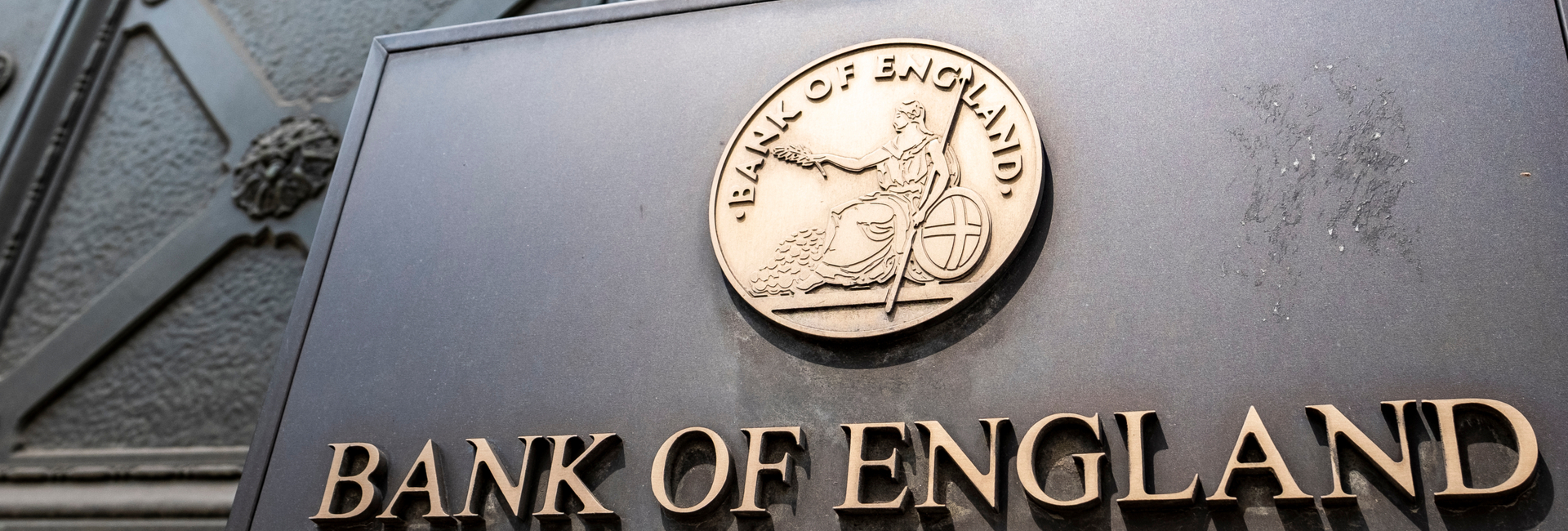 """sign with """"Bank of England"""" and bank's insignia in gold letters on black background"""