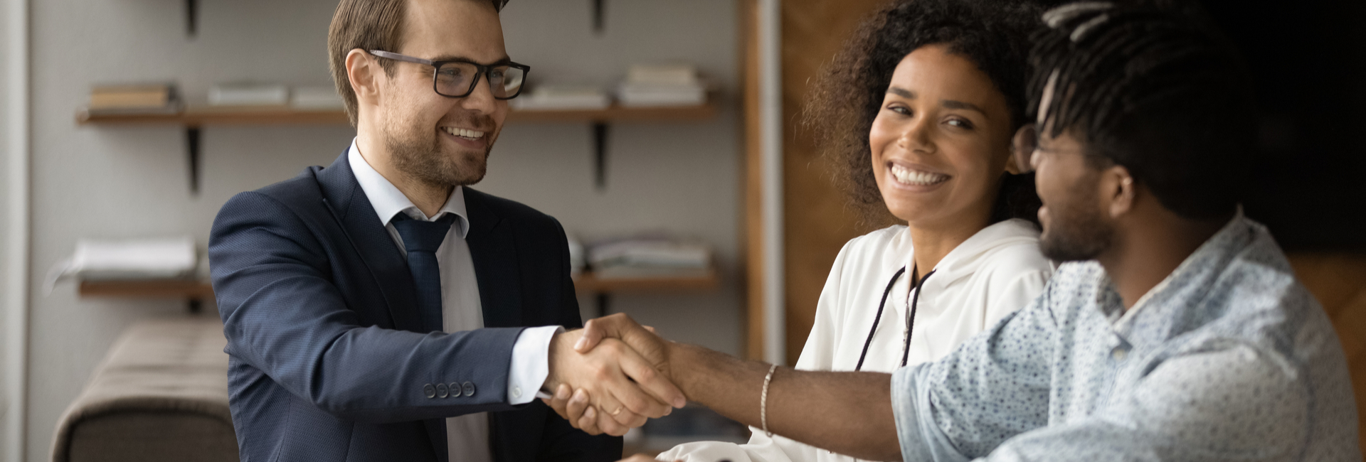 young couple shake hands with mortgage broker